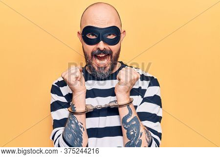 Young handsome man wearing burglar mask and handcuffs screaming proud, celebrating victory and success very excited with raised arms