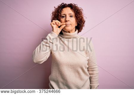 Middle age beautiful curly hair woman wearing casual turtleneck sweater over pink background mouth and lips shut as zip with fingers. Secret and silent, taboo talking