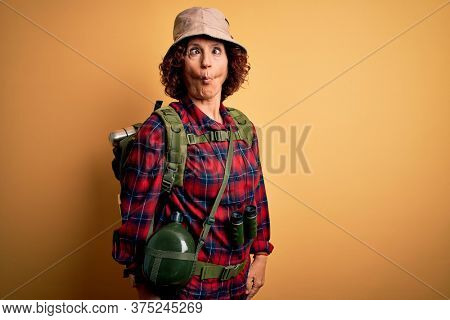 Middle age curly hair hiker woman hiking wearing backpack and water canteen using binoculars making fish face with lips, crazy and comical gesture. Funny expression.