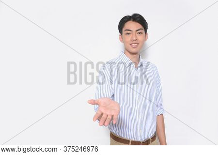 Young handsome casual man wearing striped long sleeved shirt with khaki pants showing something