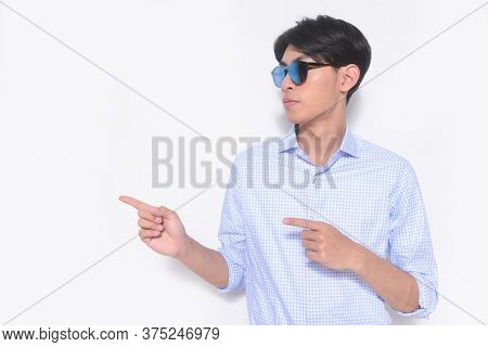 Young handsome casual man wearing sunglasses with striped long sleeved shirt, pointing with hand and finger up to the side