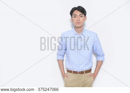 Young handsome casual man wearing striped long sleeved shirt with khaki pants and holds pockets