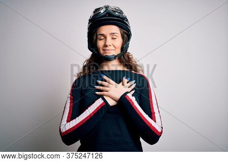 Beautiful motorcyclist woman with curly hair wearing moto helmet over white background smiling with hands on chest with closed eyes and grateful gesture on face. Health concept.