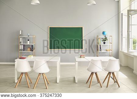 Empty School Classroom Interior With Desks And Chairs, Space For Text On Chalkboard. Modern Schoolro