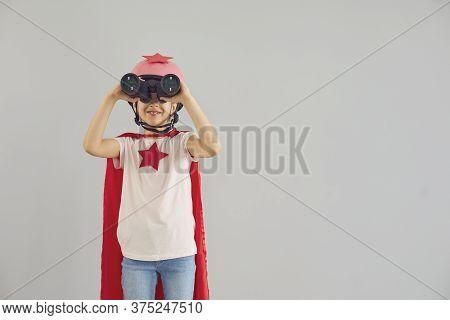 Child Wearing Superhero Costume And Looking Into Binoculars On Grey Background. Cute Girl Pretending