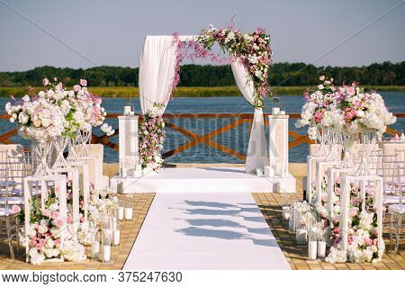 A Wedding Ceremony, A Wedding Arch, A Wedding Arch Of Twigs, Flowers And Greenery Stands On The Gree