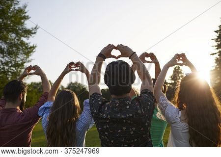 Hand Sign Heart. A Group Of People Holds Hands With A Heart Sign On A Sky Background With Sunset On
