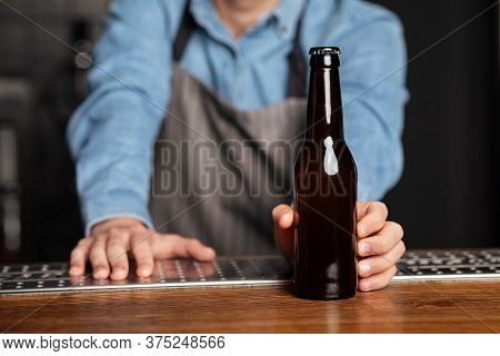 Barman In Apron Rests On Wooden Bar Counter And Serves Bottle Of Beer Without Label, Close Up, Cropp