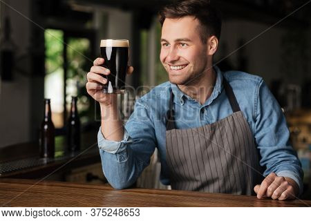 Great Taste. Smiling Handsome Barman Holds Glass Of Dark Beer In Hand And Looks At It, On Window In