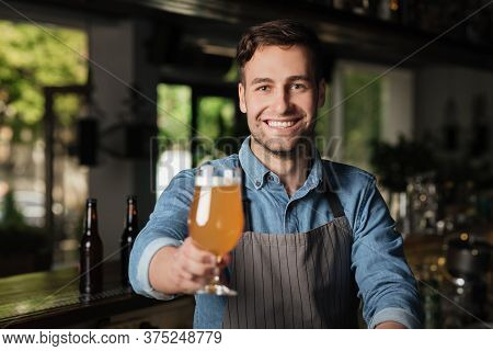 Light Lager In Glass. Smiling Bartender Holds Out Hand With Glass Of Light Beer, For Client In Inter