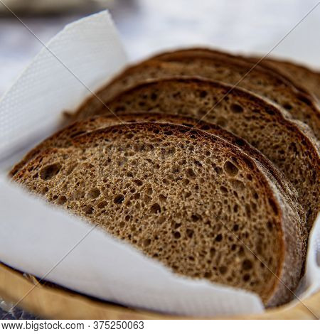 Slices Of Dark Rye Bread Lie On A Paper Napkin Outdoors On A Sunny Day. Cooking Food.