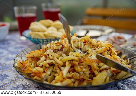 Dish With Fried Potatoes Stands On A Table Outdoors On A Sunny Day. Cooking Food.