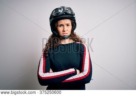 Beautiful motorcyclist woman with curly hair wearing moto helmet over white background skeptic and nervous, disapproving expression on face with crossed arms. Negative person.