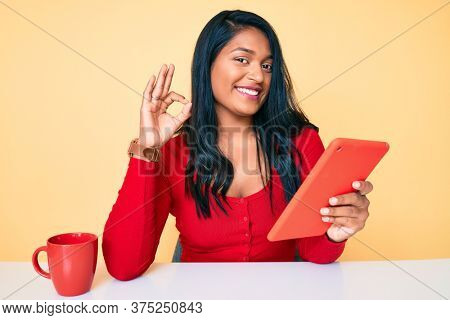Beautiful latin young woman with long hair using touchpad sitting on the table doing ok sign with fingers, smiling friendly gesturing excellent symbol