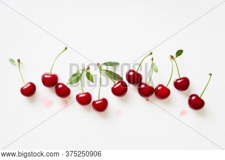 Bunch of fresh cherries with leaves on white background