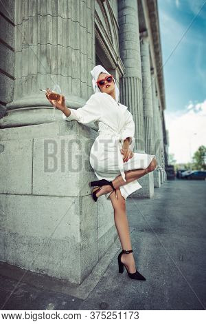 Glamorous lifestyle. Stunning woman in a white terry dressing gown with a white towel on her head and high heels alluring on a city street with a glass of champagne and cigarette. Fashion shot.