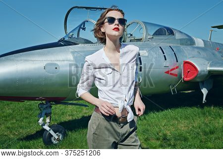 Portrait of a beautiful pilot girl standing next to her fighter plane at the airfield.
