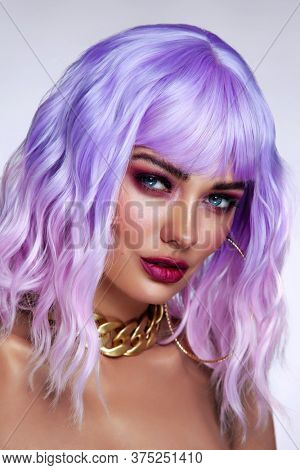 Potrait of young beautiful tanned woman with lilac hair and bright fancy makeup