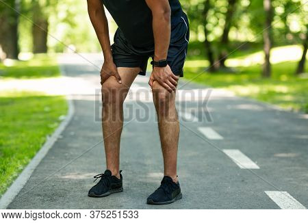 Unrecognizable Millennial Jogger Resting During His Morning Run At Summer Park, Closeup Of Legs