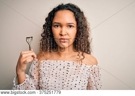 Young beautiful woman with curly hair holding eyelases curler over white background with a confident expression on smart face thinking serious