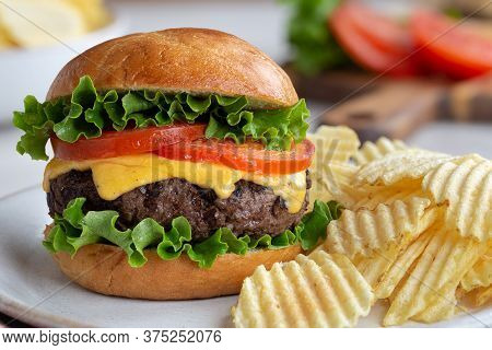 Juicy Grilled Cheeseburger With Lettuce And Tomato And Potato Chips On A Plate