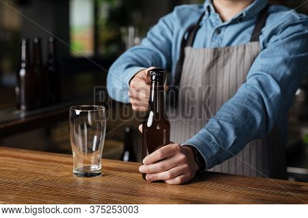 Trendy Pub And Brewery. Barman In Apron Opens Bottle Of Beer, Empty Glass Near, Cropped