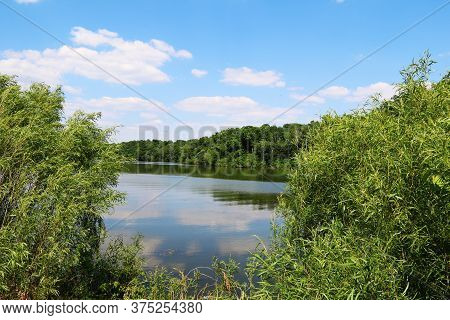 A Rural Pond With Sky Reflection And Trees With Bright Clouds