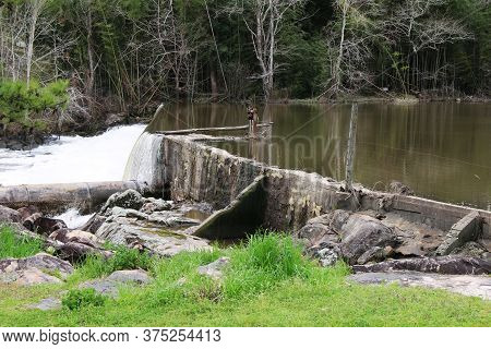 A Very Old River Dam Weir Near A Grassy Field With Forest Beyond