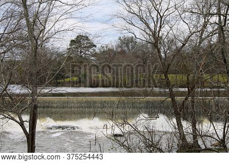 A Long Wide River Dam Weir With Autumn Trees