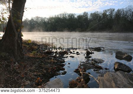 Early Morning Sunrise Reflection Over A Misty River With Rocks