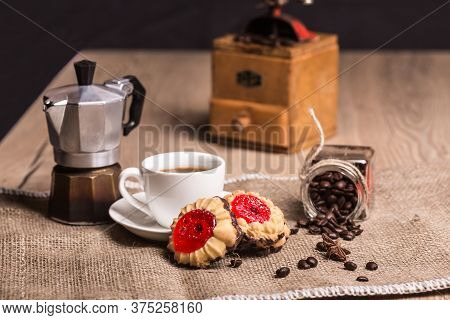 On A Rough Burlap Is Coffee Maker Mocha, Vintage Grinder, Glass Jar With Roasted Coffee Beans And St