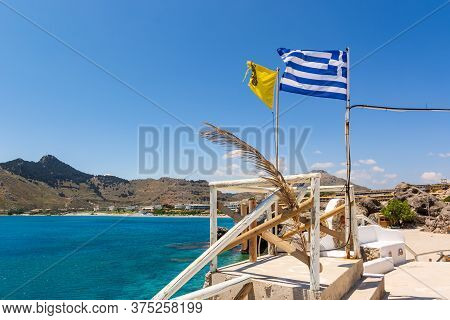 Greek Flag On Terrace Overlooking Blue Sea. Kolymbia On Rhodes Island. Greece