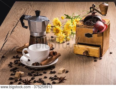 On Wooden Table Is A Coffee Maker Mocha, Vintage Coffee Grinder. White Saucer With A Cup Are Cinnamo