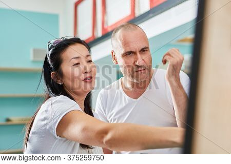 Artist couple looks at a picture on the easel in the studio or in the art academy