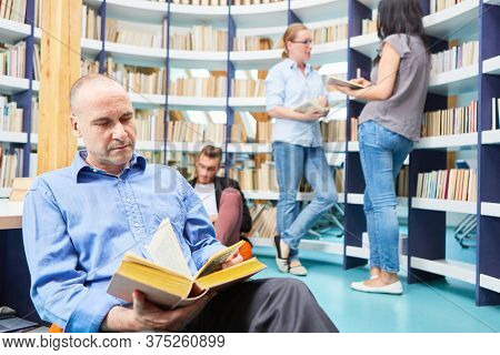Man as a lecturer reading the book in the reading room of the library in the community college