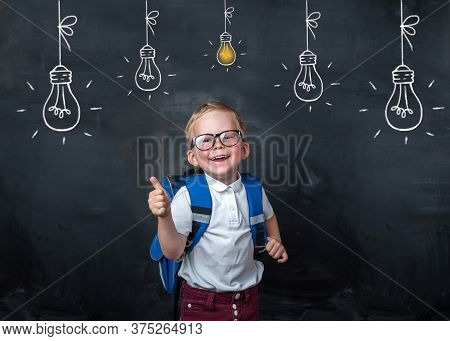 Back To School. Funny Little Boy In Glasses Pointing Up On Blackboard. Child From Elementary School