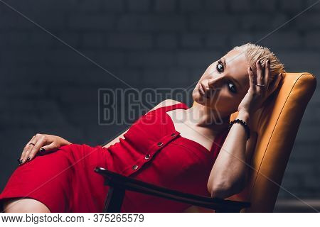 Young Woman With Blonde Hair And A Short Haircut In A Red Evening Dress Lies On The Chair