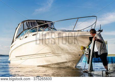 Big Luxury Cabin Motorboat Cruiser Yacht Launching At Trailer Ramp On River Or Lake. Mechanic Worker