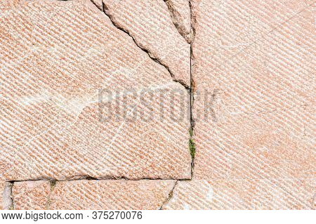 Road Red Tile With Cracks And Sprouted Grass. Abstract Background. Copyspace. Close-up