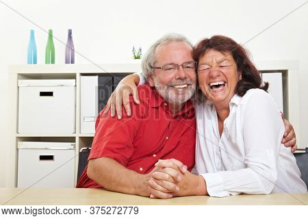 Two laughing seniors hug in the living room
