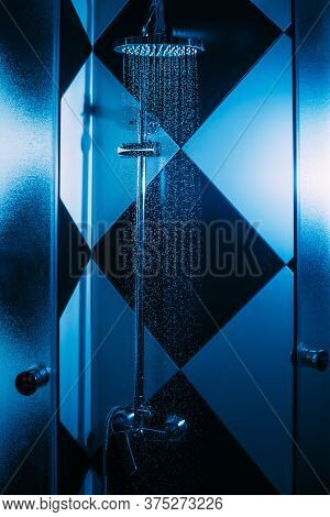 Drops Of Water Fall From A Watering Can In The Shower In Blue Light. Water Drops Close-up. Flow Of W