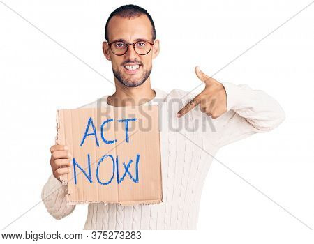 Young handsome man holding act now banner pointing finger to one self smiling happy and proud