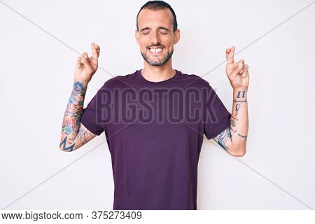 Young handsome man with tattoo wearing casual clothes gesturing finger crossed smiling with hope and eyes closed. luck and superstitious concept.