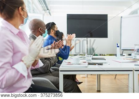 Business people in a seminar on online video communication with monitor clap applause
