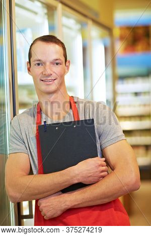 Retail salesman stands with clipboard leaning against chilled shelf in supermarket