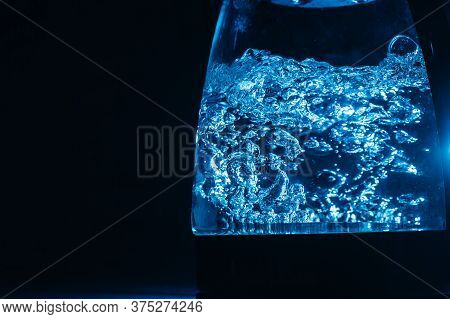 Boiling Glass Black Teapot With Blue Backlight On A Black Background. Boiling Water. Hot Water Is Se