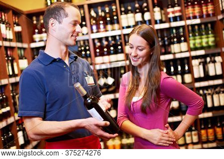 Seller in the supermarket recommends a bottle of red wine to a woman