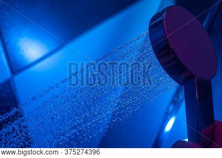 Girl Holds A Watering Can In A Shower Cabin With Blue Backlight. Falling Drops Of Water From A Water