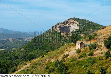 a view of a mountain landscape at Olmeta-di-Tuda, facing North, on the North of Corse, France, with a disused quarry in the background