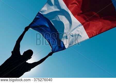 closeup of the silhouette of a young man holding a French flag waving on the wind against the blue sky, in backlit
